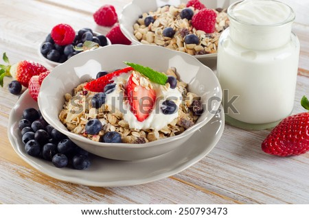 Breakfast with ripe berries, yogurt and  muesli. Selective focus - stock photo