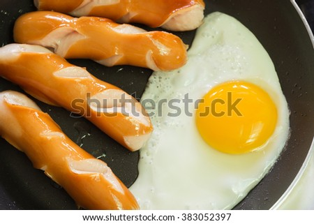Breakfast with sausage and fried egg on frying pan - stock photo