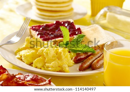 breakfast with scrambled eggs, sausage links and toast. - stock photo
