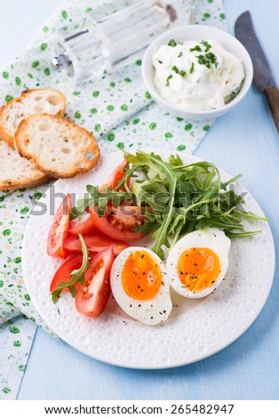 Breakfast with soft-boiled egg, arugula, soft cheese and tomatoes, selective focus - stock photo