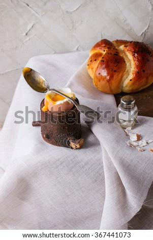 Breakfast with started eating soft-boiled egg with pouring yolk in wooden eggcup and bread served with salt and spoon on wooden chest with white cloth over table. With plastered wall at background - stock photo