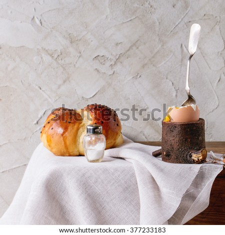 Breakfast with started eating soft-boiled egg with pouring yolk in wooden eggcup and bread served with salt and spoon over white cloth. With plastered wall at background. Square image - stock photo