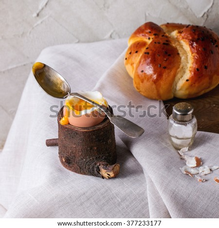 Breakfast with started eating soft-boiled egg with pouring yolk in wooden eggcup and home made bread served with salt and spoon on wooden chest with white cloth. Square image with selective focus - stock photo