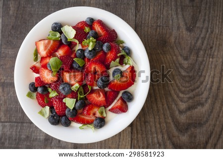 Breakfast with strawberry, blueberry, basil leaves and yogurt. - stock photo