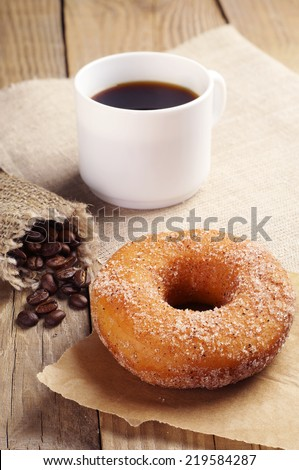 Breakfast with sweet donut and coffee on wooden table - stock photo
