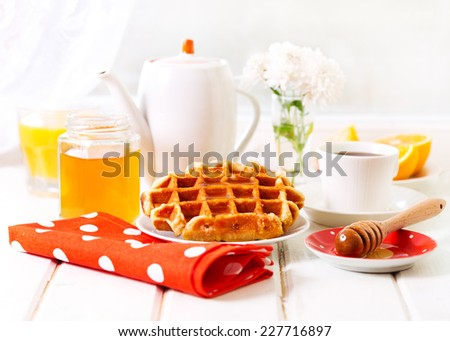 breakfast with waffles, honey and coffee on wooden table - stock photo