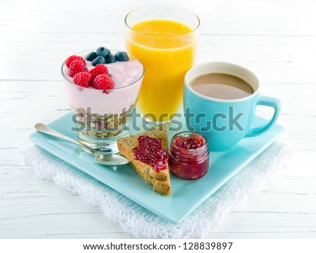 Breakfast with yoghurt, berries, juice, toast and coffee, on white wooden background - stock photo