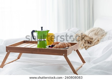 Breakfast wooden tray with coffee percolator and croissant on bed, sleeping woman background. Focus on coffee maker. - stock photo