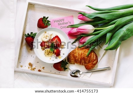 Breakfast yogurt bowl with strawberries and bananas served in a white tray with croissant Mother's day note and tulip flowers / Mother's day Brunch top down view - stock photo