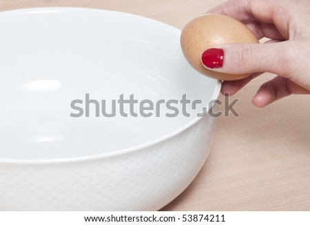 Breaking an egg into a bowl - stock photo
