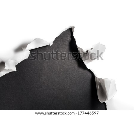 Breakthrough paper hole with blackboard background. - stock photo