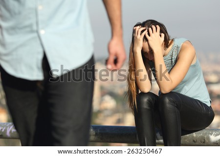 Breakup of a couple with bad guy and sad girlfriend with a city in the background - stock photo