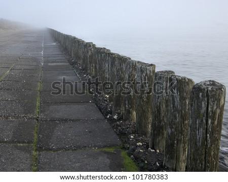 breakwater in fog near Terneuzenn (Netherlands) - stock photo