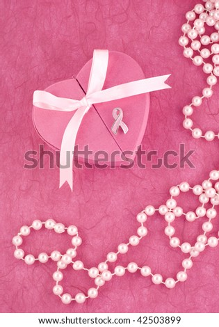 Breast Cancer Awareness Ribbon Pin on a pink heart shaped jewelry box with pink background and pearls, vertical with copy space - stock photo