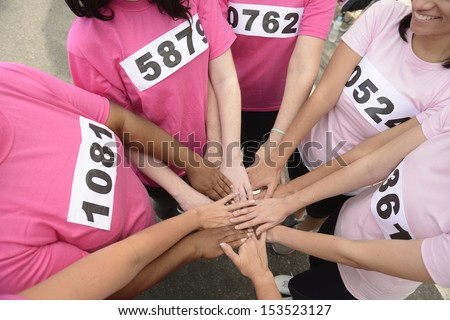 breast cancer awareness: women joining hands for support  - stock photo