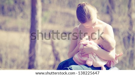 breastfeeding. mother feeding her baby in nature outdoors in the park - stock photo