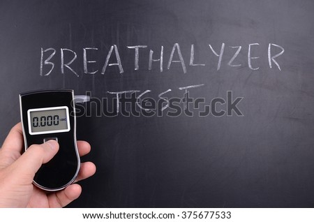 Breathalyzer test and blackboard - stock photo