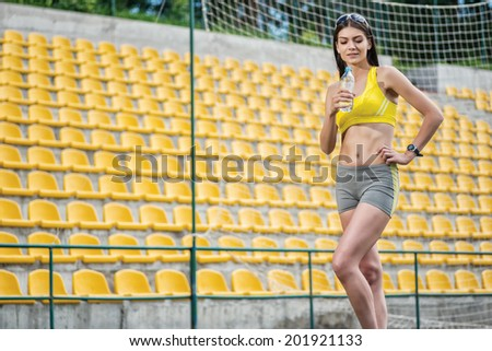 Breathing space in  training and drinking water. Woman in tracksuit holding a water bottle on the football field on a sunny day in sunglasses - stock photo