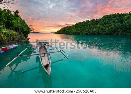 Breathtaking colorful sunset and traditional boat floating on scenic blue lagoon in the Togean (or Togian) Islands, Central Sulawesi, Indonesia, upgrowing travel destination. - stock photo