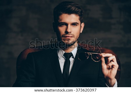 Breathtaking look.Portrait of young handsome man in suit holding his sunglasses and looking at camera while sitting in leather chair against dark grey background - stock photo