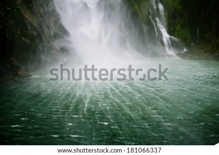 breathtaking ripple from spectacular waterfall - roar sound white splash green ocean - Milford Sound, New Zealand - stock photo