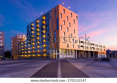BREDA, NETHERLANDS - MARCH 7: Apartment buildings at the Chasseveld at dusk, illuminated during twilight, modern architecture build in the dutch city center , on March 7, in Breda, Netherlands - stock photo