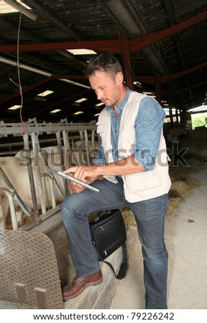 Breeder in barn with electronic tablet - stock photo