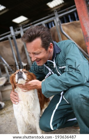 Breeder petting dog outside the barn - stock photo