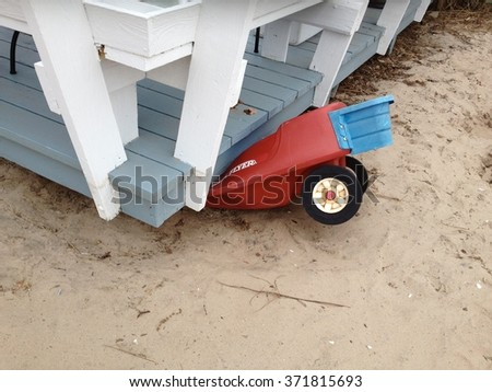 BREEZY POINT, QUEENS, NY-December 2, 2012: Breezy Point debris from home damaged by waves and storm surge by Hurricane Sandy. Photo  reveals child's toy cart pinned under deck in Queens, NY. - stock photo