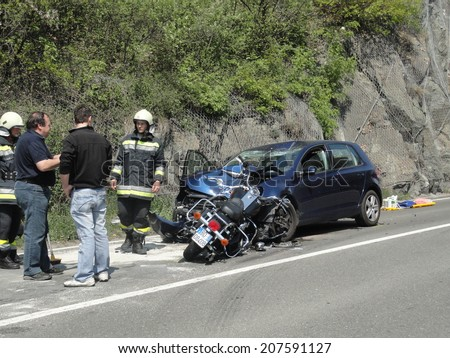 BRESSANONE BRIXEN, APRIL 4, 2011: Firefighters at work after frontal accident between a motorcyclist and a car. Motorbike crash collision hit by car on the road in Bressanone Brixen on April 4, 2011 - stock photo
