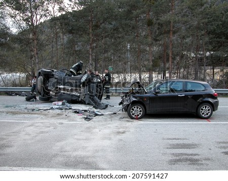 BRESSANONE, ITALY - APRIL 5, 2013: Firefighters and Paramedics at work after collision between two cars on the road. Car crash turned upside-down in Bressanone on April 5, 2013 - stock photo