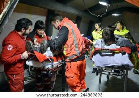 BRESSANONE, ITALY - NOVEMBER 16, 2014: A doctor examines patients at a free medical camp for flood affected victims. Hospital field tent for the first AID on November 16, 2014. - stock photo