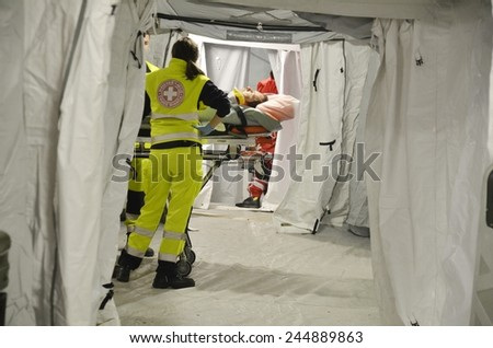 BRESSANONE, ITALY - NOVEMBER 16, 2014: Patient waiting for a doctor on the stretcher inside a hospital field tent for the first AID. Camp room for the rescue of injured people on November 16, 2014. - stock photo