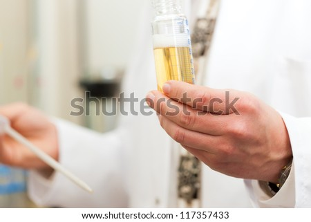Brewer in the laboratory of his brewery and is doing analysis - stock photo