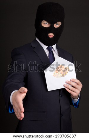 bribery concept - man in suit and mask with money in white envelope ready to handshake - stock photo