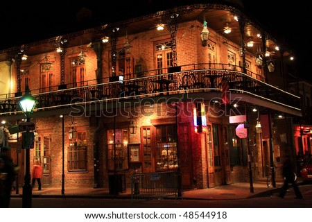 Brick building with balcony on the corner of St. Peter and Bourbon Streets at night in the French Quarter of New Orleans, LA - stock photo