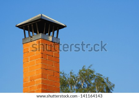 Brick chimney against the tree and the blue sky - stock photo