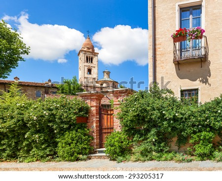 Brick fence covered with green bushes and parish church on background in small town in Piedmont, Northern Italy. - stock photo