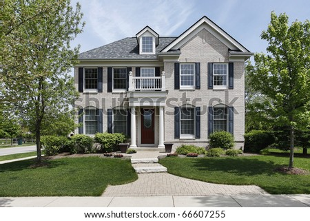 Brick home with front columns and balcony - stock photo