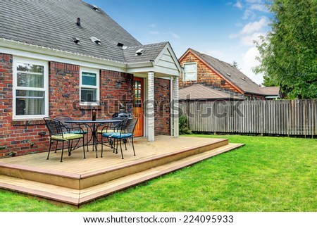 Brick house with walkout wooden patio area - stock photo