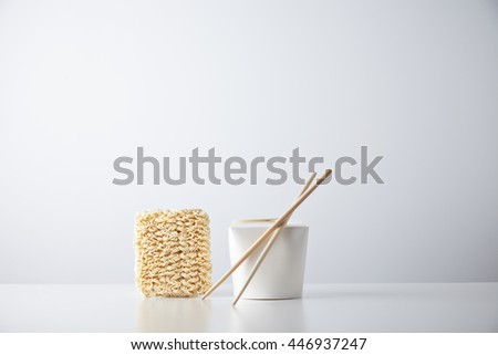 Brick of dry japanese noodles presented near closed blant retail takeaway box with chopsticks, isolated on white - stock photo