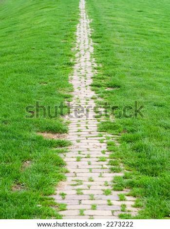 Brick path on a green dike. - stock photo