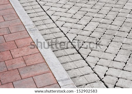 Brick paving types with pink sidewalk, curb and drive made from plain interlocking concrete bricks - stock photo