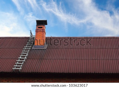 Brick roof chimney and a ladder - stock photo