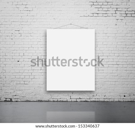 brick room with blank poster on wall - stock photo