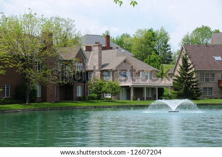 Brick Suburban Lake front Homes in the summer. - stock photo
