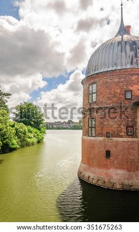 Brick tower in the lake surrounding Castle Frederiksborg Slot, Hillerod, near Copenhagen, Denmark - stock photo