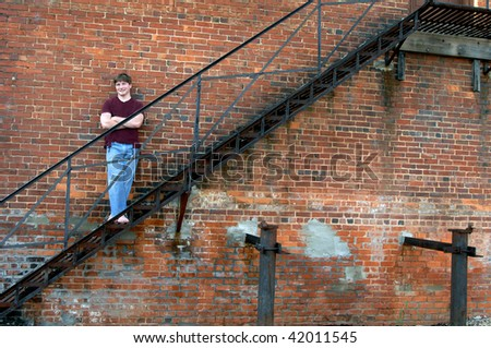 Brick wall and fire escape serves as a resting place for young teen.  He is wearing jeans with hole at knee and a torn burgundy tee shirt. - stock photo