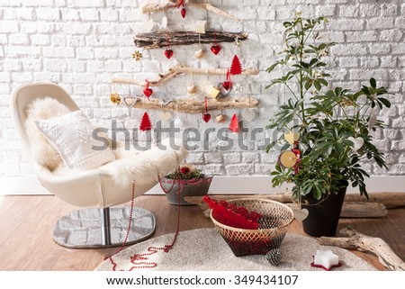 brick wall Christmas tree with modern armchair - stock photo
