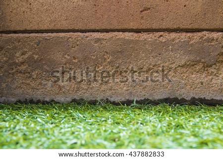 brick wall on grass field. - stock photo
